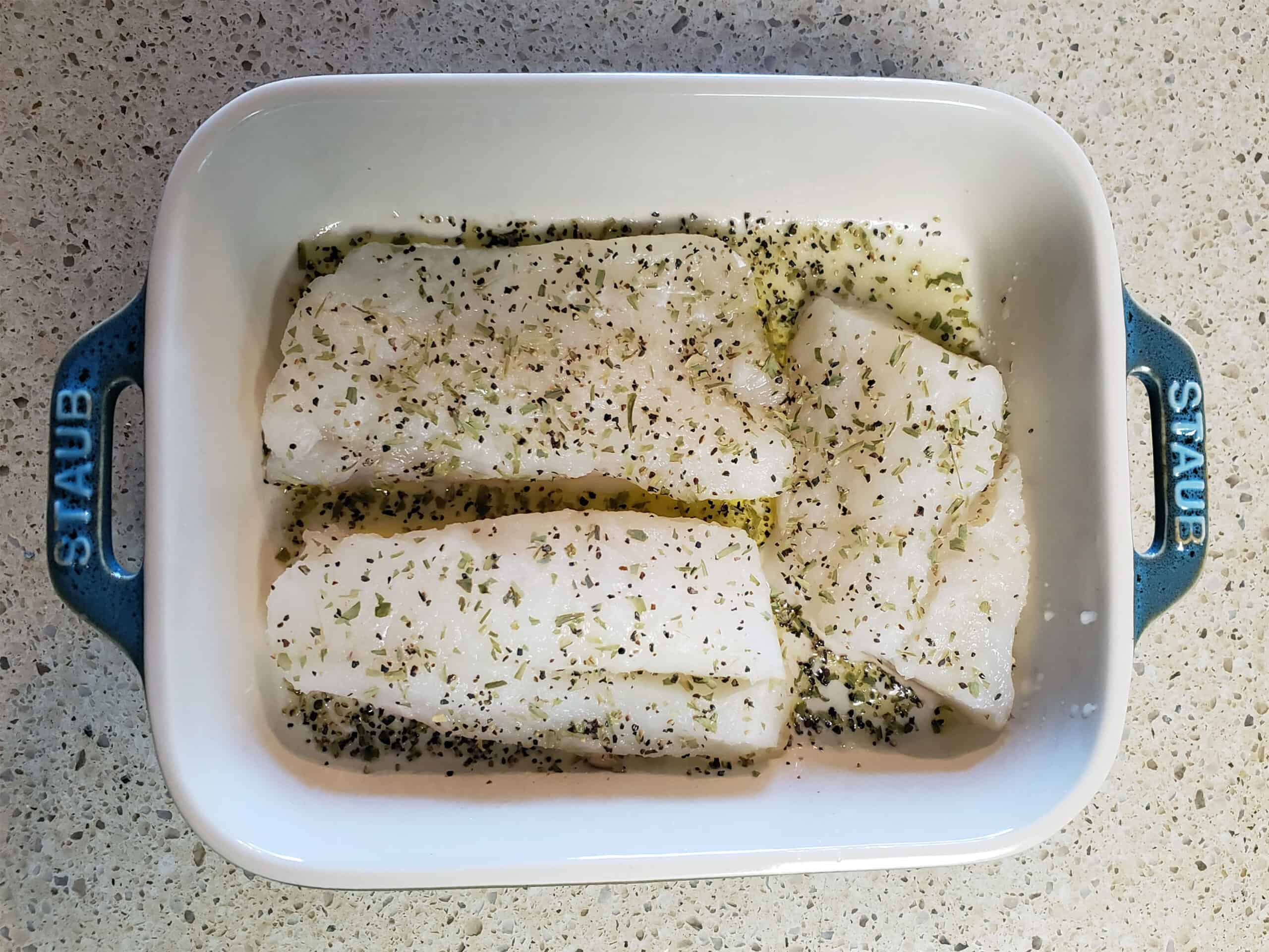 Seasoned tilapia fillets in baking dish