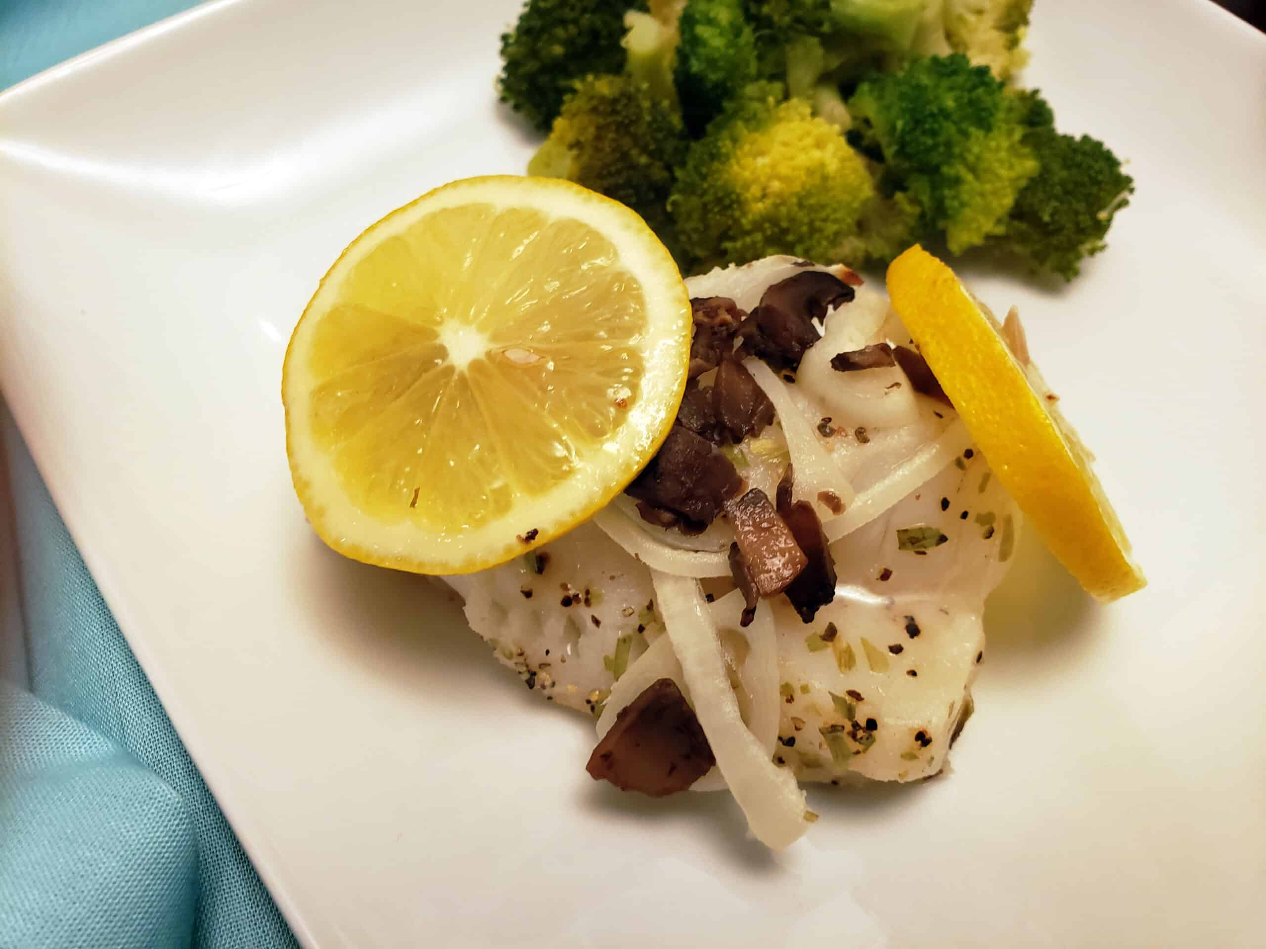 baked tilapia with lemon tarragon sauce om white plate with broccoli