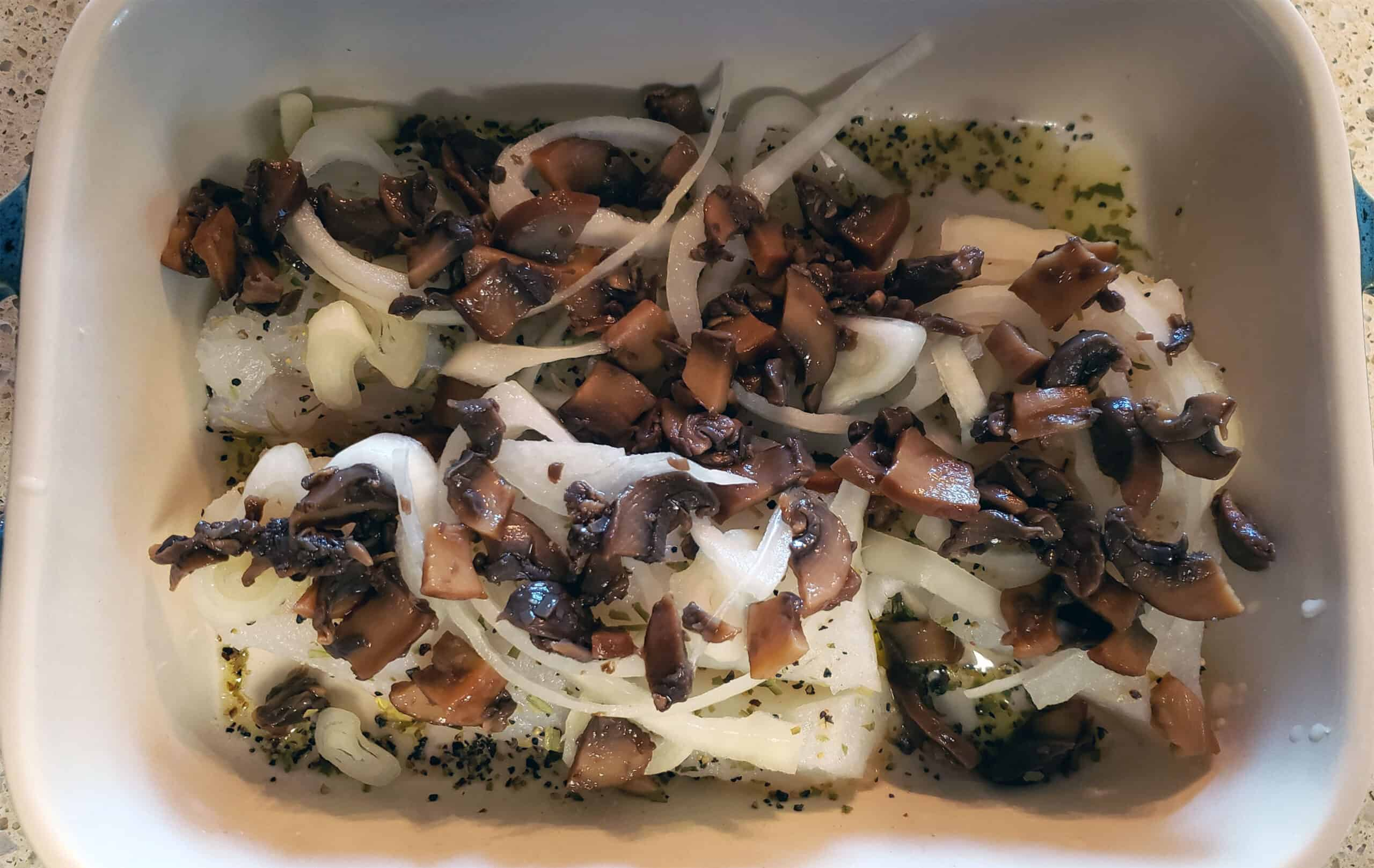 tilapia with mushrooms and onions in baking dish
