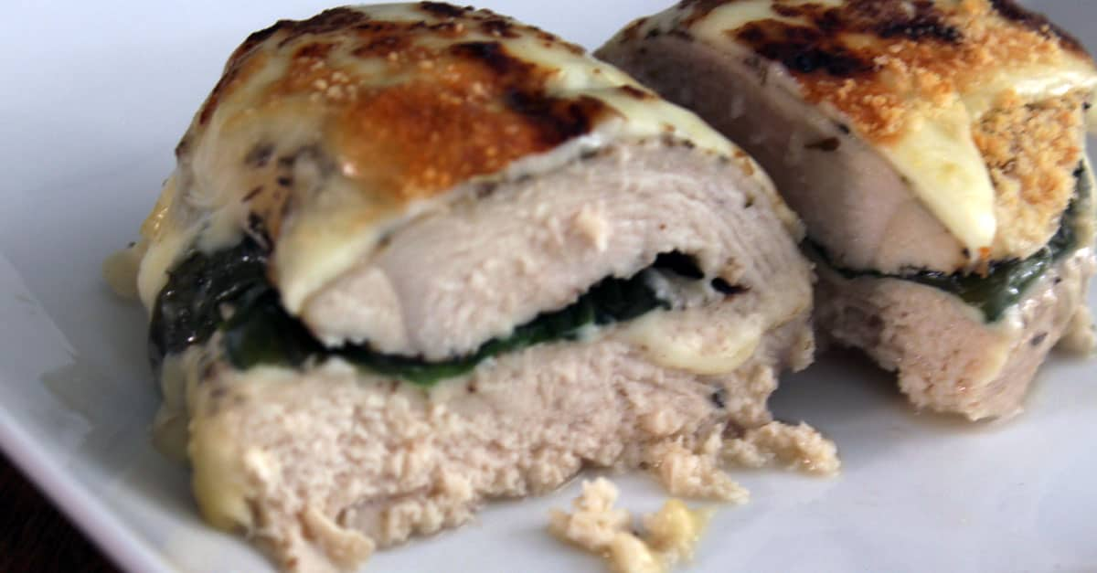 Stuffed, baked chicken on white plate