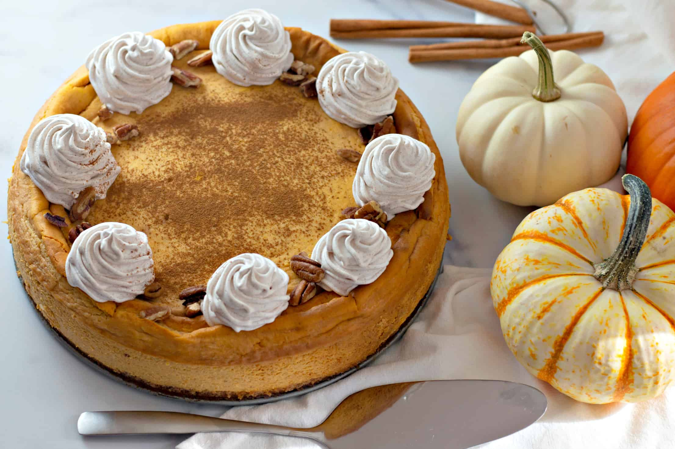 keto pumpkin cheesecake on white counter with mini pumpkins