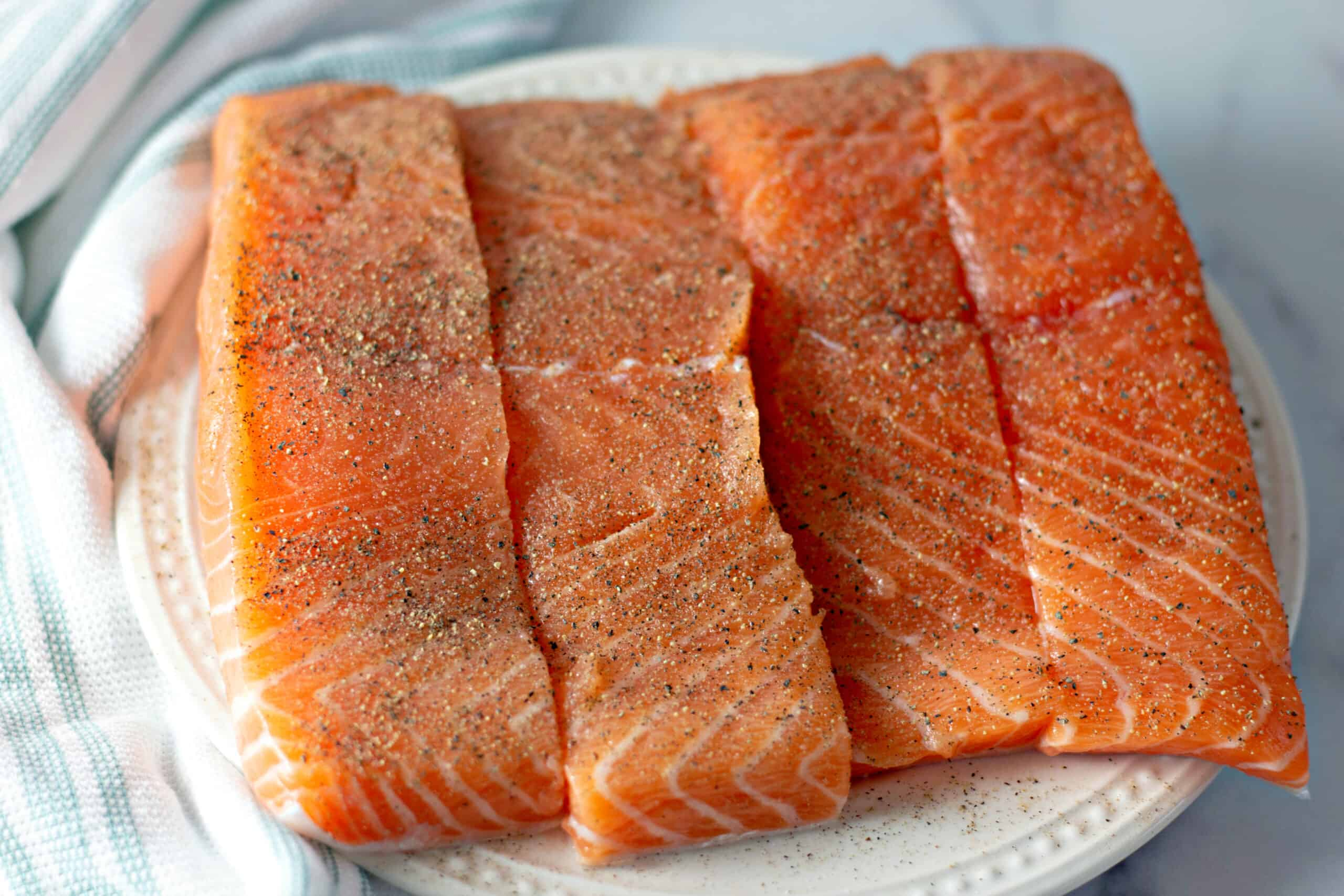 seasoned salmon fillets on white plate